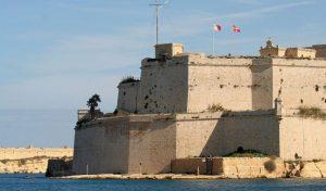 Bendera Ordo Militer Berdaulat Malta berkibar bersamaan dengan bendera Republik Malta di Benteng Saint Angelo, Birgu, Malta